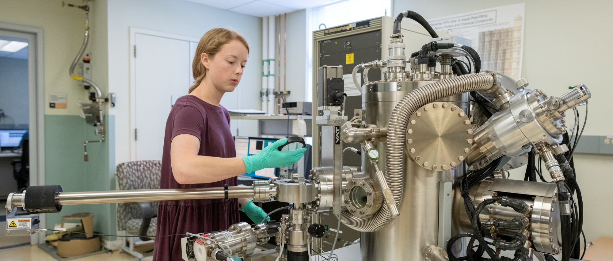 Student loading sample into the x-ray photoelectron spectroscopy (XPS) tool.